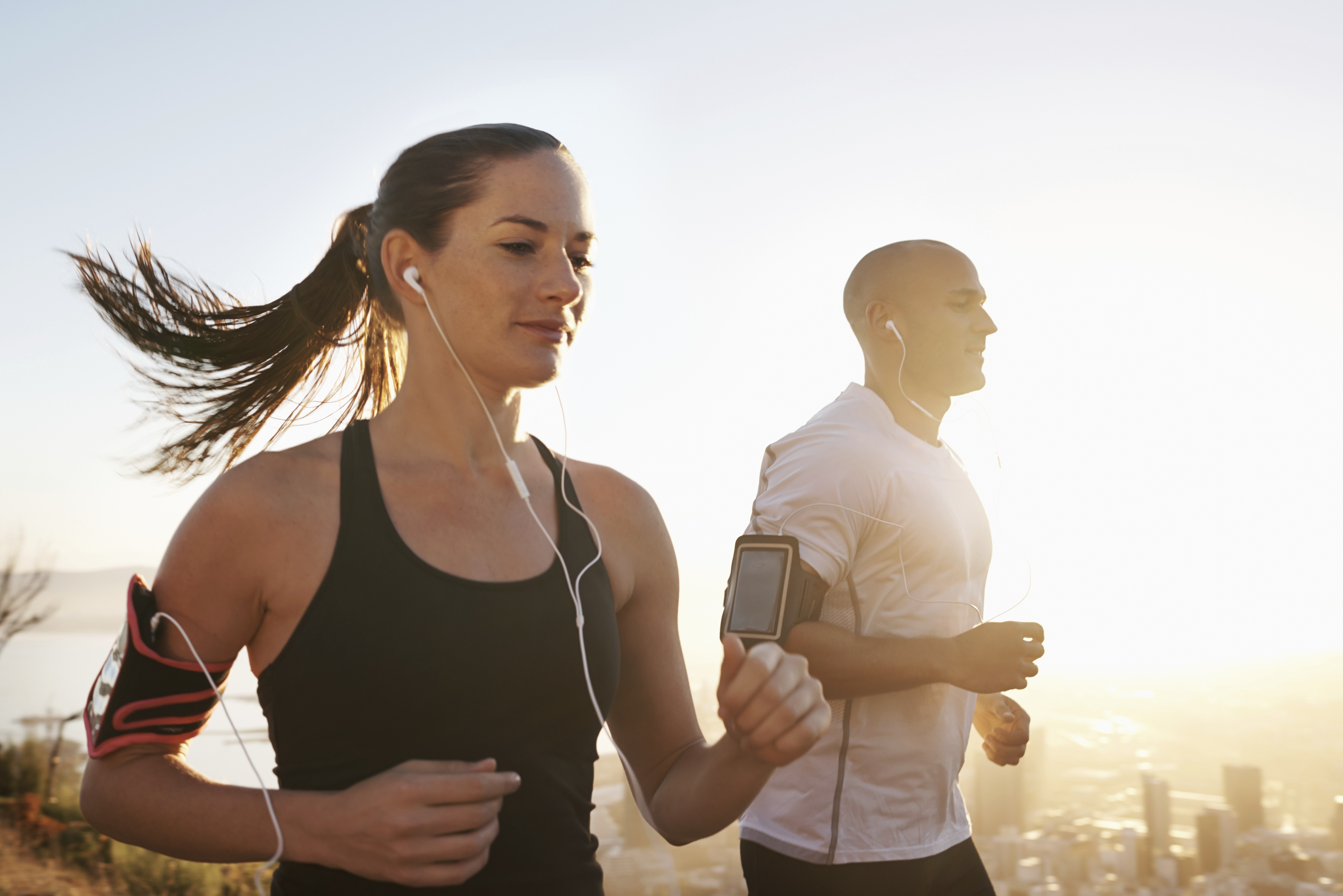 Cropped shot of two young athletes running while listening to music